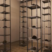 """Mahsa Aleph, """"Corpse"""", from """"The Container made of the Contained"""" series, installation made of thirty-five thousand date kernels in 4 metal columns consists of 10 shelves, processed by turmeric, mold, oil, and soot, 2019"""