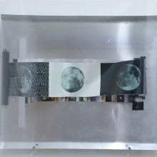 """Arya Tabandehpoor, """"Day, Night, Noise"""", from """"Retooling"""" series, (part of a photo-cutting machine, photographs printed on a metallic paper, offset plate, wooden frame, translucent plexiglas, adaptor, on-off switch, double-sided tape, screw, washer, green ink, 90 degrees' brace), 70 x 75 cm, 2019"""
