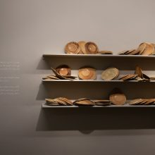 """Mahsa Aleph, from """"The Container made of the Contained"""" series (Detail), installation of 700 plates in wooden shelves, bread dough, variation of 1000-1699, 2019"""