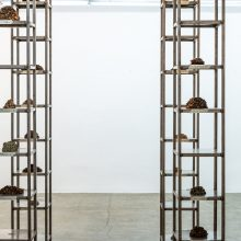 """Mahsa Aleph, """"Corpse"""" , from """"The Container made of the Contained"""" series, installation made of thirty-five thousand date kernels in 4 metal columns consists of 10 shelves, processed by turmeric, mold, oil, and soot, installation view, 2019"""