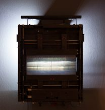 """Arya Tabandehpoor, untitled, from """"Retooling"""" series, (printed photograph on transparent sheet, metal frame, stepper motor, arduino board, drivers, wires, switch, ball bearing, screws, power adaptor, roller, double-sides tape, rail, belt), unique edition of 7, 32.5 x 38 x 5 cm , 2018"""